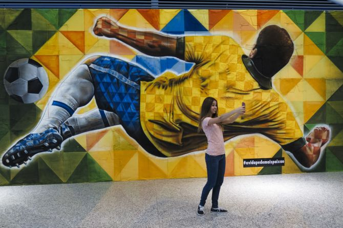 A girl takes a selfie before a mural depicting a player kicking the ball.