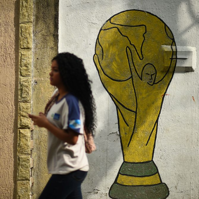 A girl walks past a mural depicting the World Cup trophy on the streets of Brazil.
