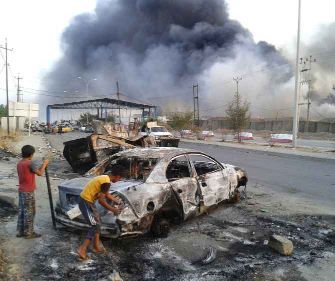 Children stand next to a burnt vehicle during clashes between Iraqi security forces and al Qaeda-linked militants in Mosul