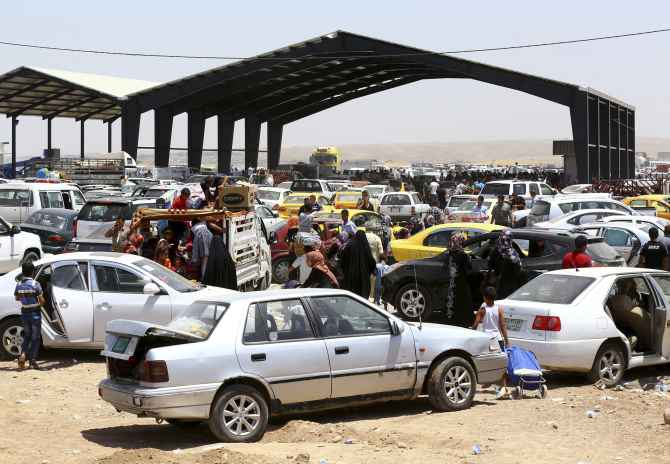 Families fleeing the violence in Mosul arrive at a checkpoint in outskirts of Erbil