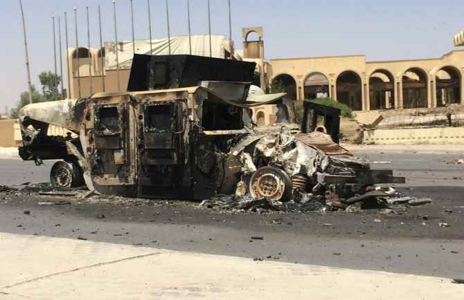 A burnt vehicle belonging to the Iraqi security forces is left on a road a day after insurgents seized control of Mosul