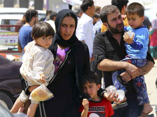 A family fleeing the violence in Mosul waits at a checkpoint in outskirts of Erbil
