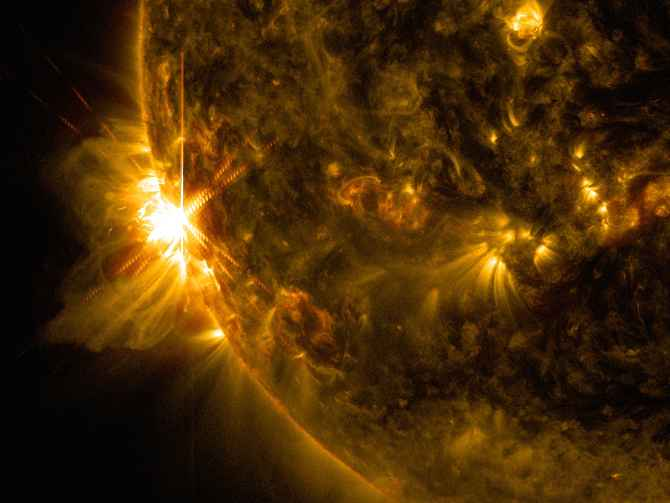 A solar flare bursts off the left limb of the sun in this image captured by NASA's Solar Dynamics Observatory