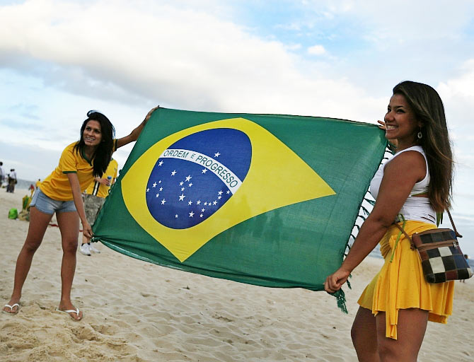 Brazilian soccer fans display a Brazilian flag before the opening match of the 2014 World Cup between Brazil and Croatia at the Copacabana beach in Rio de Janeiro