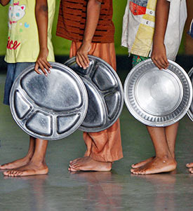Children holding plates wait in a queue to receive food at a Chennai-based orphanage run by a non-governmental organisation.