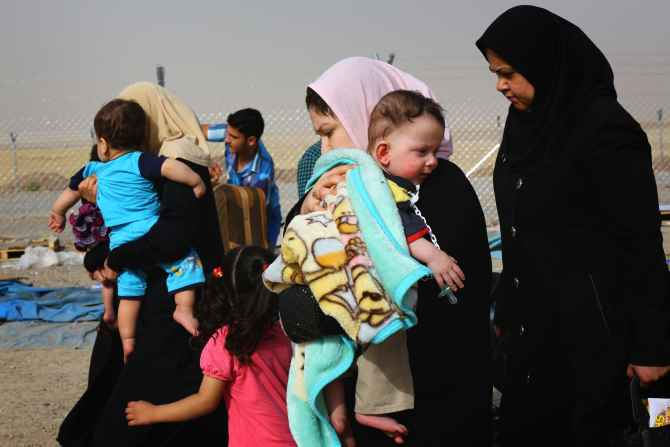 Families fleeing the violence in Mosul arrive at a checkpoint on the outskirts of Erbil on Thursday