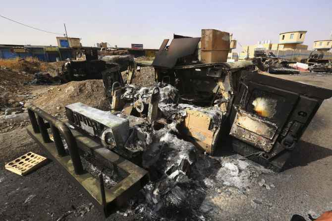 Burnt vehicles belonging to Iraqi security forces are pictured at a checkpoint in east Mosul two days after ISIL fighters took over the city