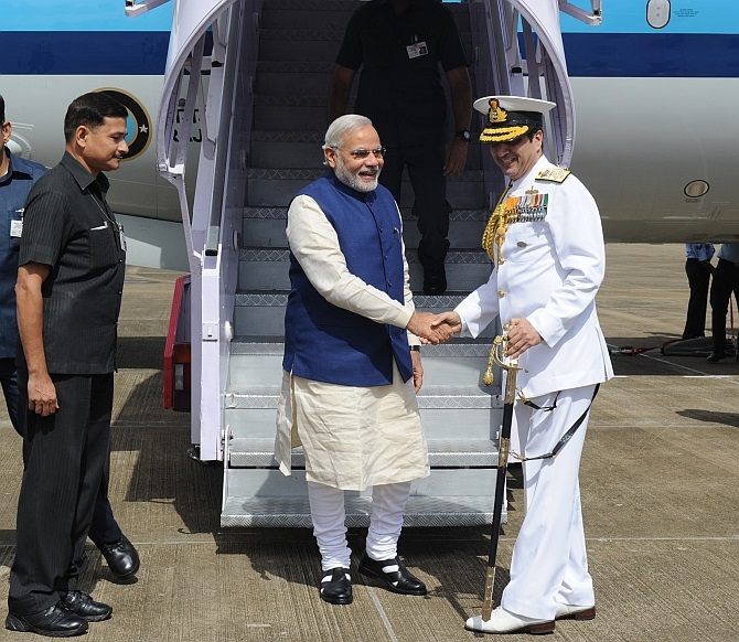 The prime minister is received by naval chief Admiral Robin K Dhowan.
