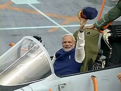 Prime Minister Modi waves after boarding a jet on board the warship.