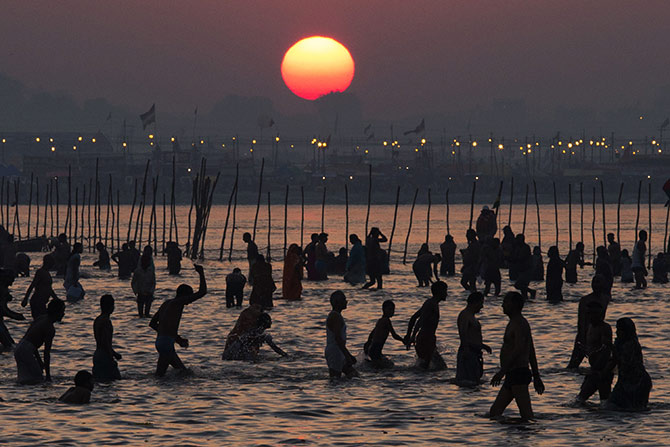 In the backdrop of the setting sun, men take a dip in the holy Sangam during the Kumbh mela in Allahabad.