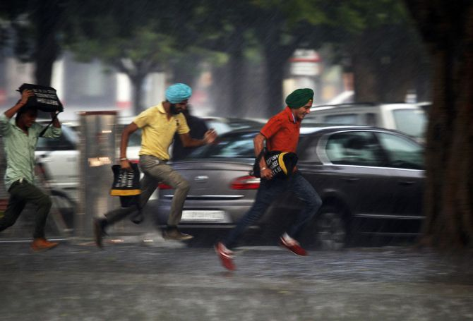 Men run for cover during a heavy rain shower in the northern Indian city of Chandigarh