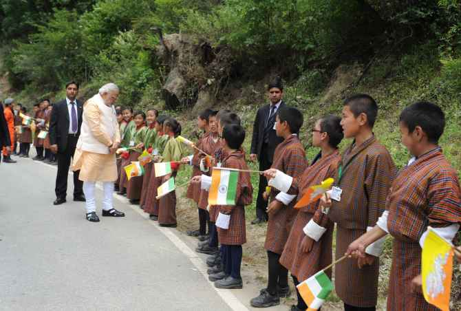 Prime Minister Narendra Modi meeting children who lined up waving flags to wish him goodbye along the road to the airport, in Thimphu
