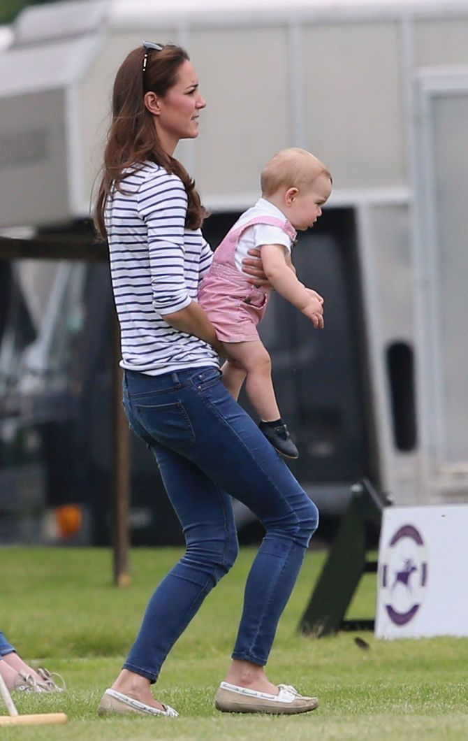 Prince George wriggles in his mother's arms trying to break free.