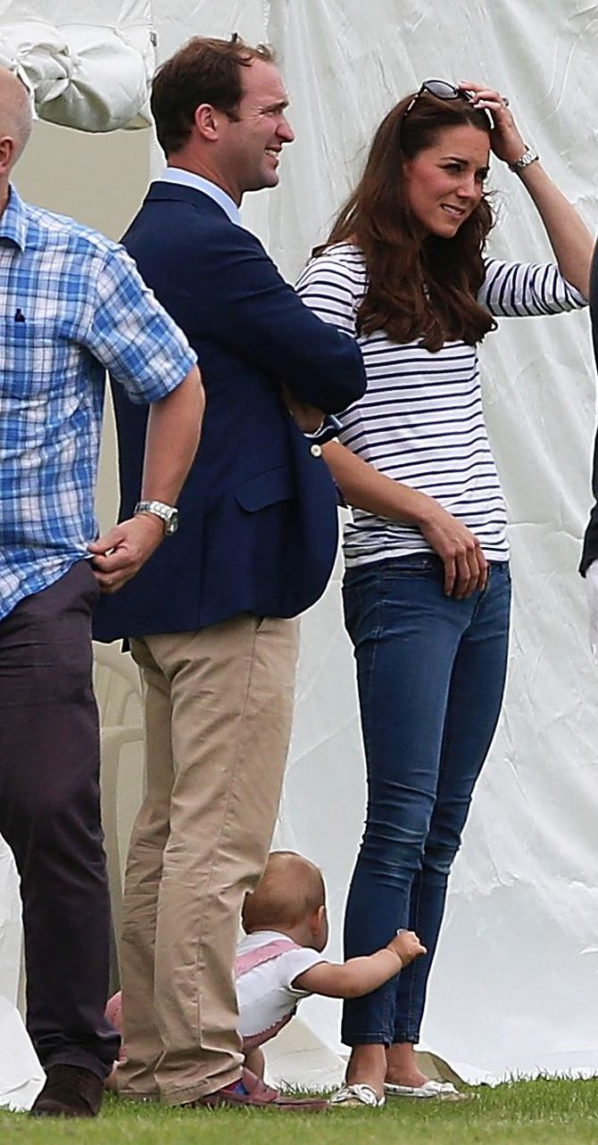 Prince George tries to get his mother's attention as she watches the Duke of Cambridge take part in the annual polo game at Cirencester Park Polo Club.