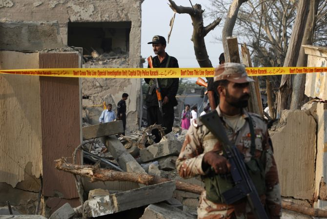 Security forces keep guard at the site of the Crime Investigation Department building the morning after it was levelled by a suicide bomb attack in Karachi in November 12, 2010