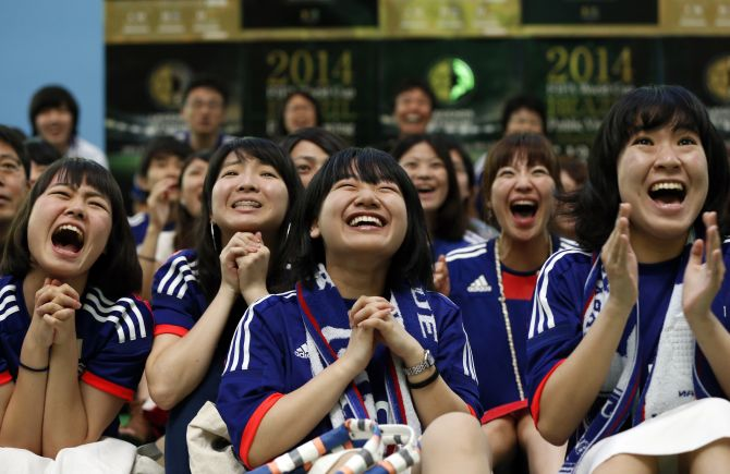 Japanese fans pray as they cheer on their team during their match against Ivory Coast at the FIFA World Cup in Brazil.