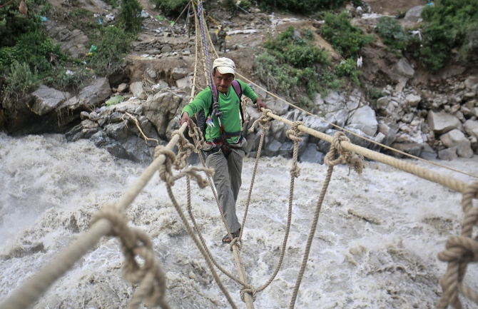 A man crosses a rope bridge over the Alaknanda river during rescue operations in Govindghat in Uttarakhand in this photograph taken on June 23, 2013.