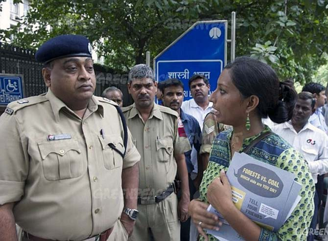 Greenpeace campaigner Priya Pillai talks to security officials during a protest against the coal ministry
