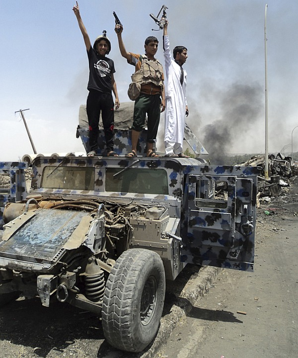 Gunmen celebrate near a vehicle belonging to Iraqi security forces in the northern Iraq city of Mosul