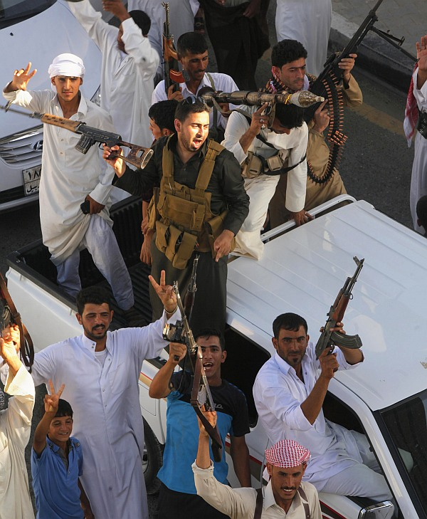 Tribal fighters shout slogans as they carry weapons during a parade on the streets of Najaf, south of Baghdad