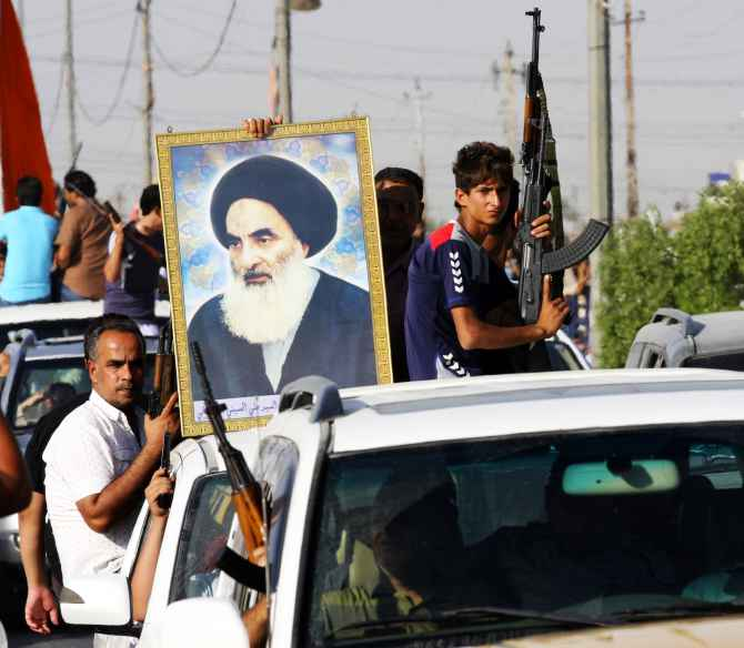 Volunteers with the Iraqi army fighting against Sunni ISIS militants, carry weapons and a portrait of Grand Ayatollah Ali al-Sistani during a parade in Baghdad