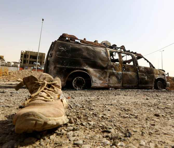 A burnt vehicle belonging to Iraqi security forces at a checkpoint in east Mosul which was taken over by ISIS fighters