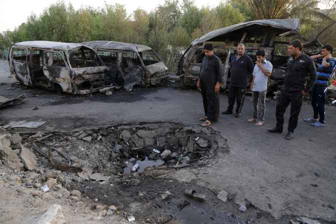 People gather at the site of an ISIS-orchestrated car bomb attack in Baghdad's Sadr City