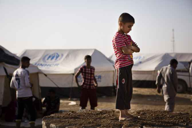 A boy, who fled from the violence in Mosul, stands near tents in a camp for internally displaced people on the outskirts of Erbil in Iraq's Kurdistan