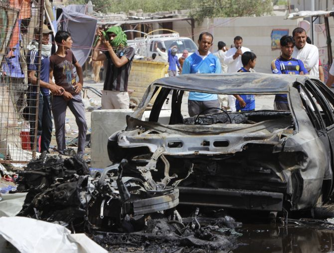 People look at the cars, which were burnt by the Sunni rebels.