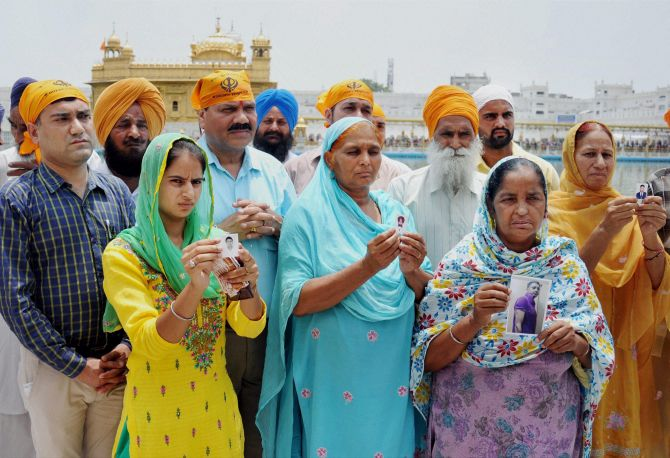Family members of the Indians who are abducted in Mosul show their pictures outside the Golden Temple, Amritsar