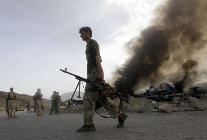 Afghan security forces leave the site of burning NATO supply trucks after an attack by militants in the Torkham area near the Pakistani-Afghan in Nangarhar Province