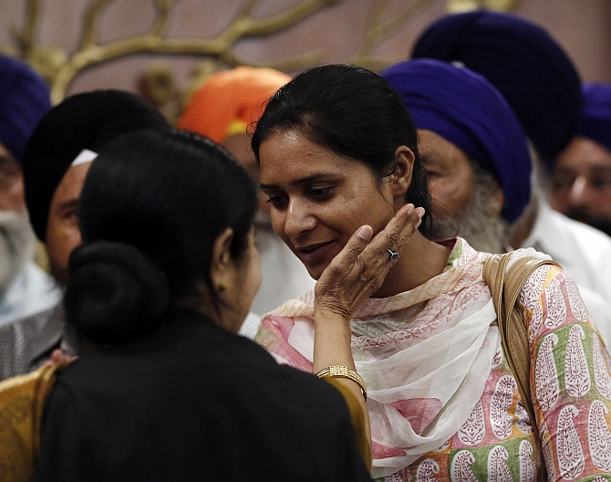 A relative of an Indian worker who has been kidnapped in Iraq, is being comforted by External Affairs Minister Sushma Swaraj after their meeting in New Delhi