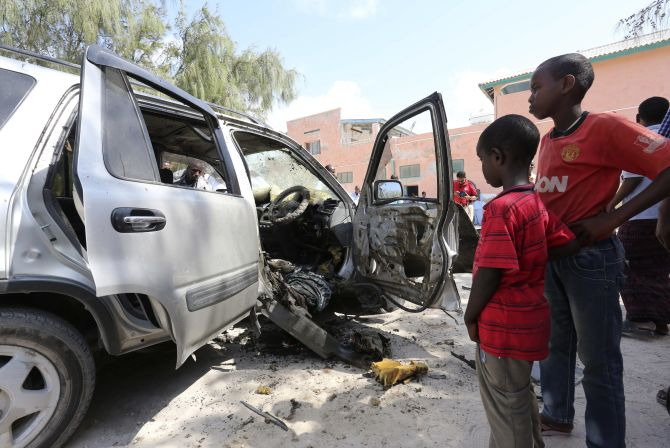 Somali boys look at the wreckage of a car belonging to Dr Mahad Abdi Xaafid in capital Mogadishu