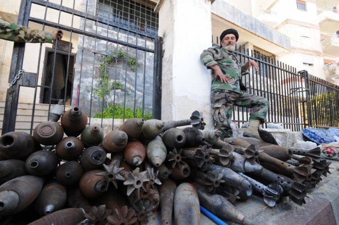 A soldier loyal to Syrian President Bashar al-Assad poses next to mortar bombs that rebels left behind, at the Armenian Christian town of Kasab