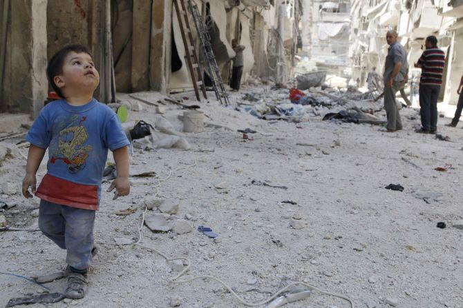 A boy walks beside debris after what activists claimed was shelling by forces loyal to Syria's President Bashar Al-Assad, in the Tariq Al-Bab neighbourhood of Aleppo