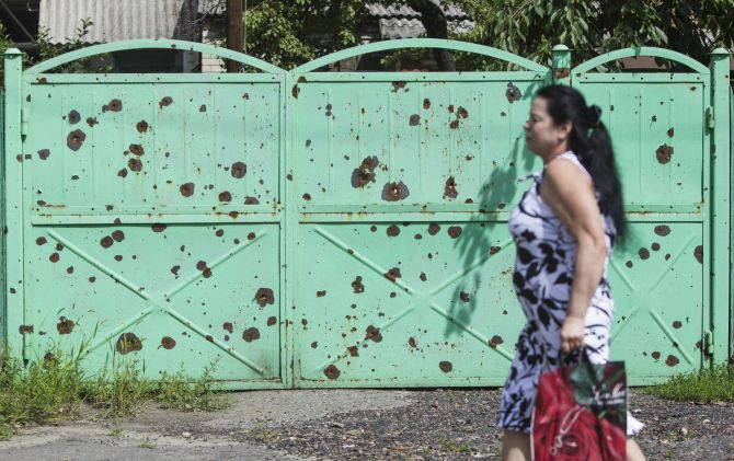 A woman walks past a gate filled with shrapnel holes, in the eastern Ukranian city of Slaviansk
