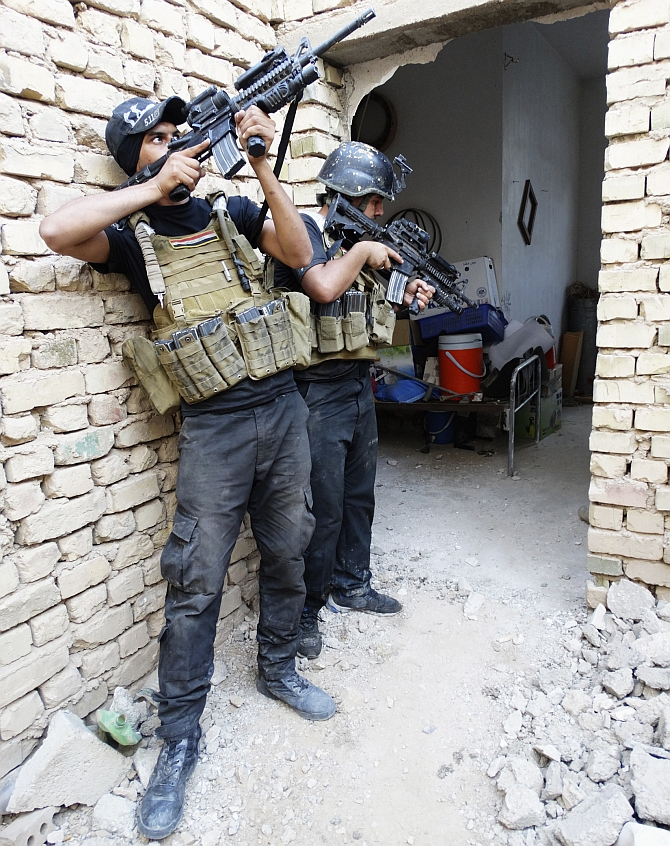 Members of the Iraqi Special Operations Forces take their positions during a patrol looking for militants, the Islamic State of Iraq and Syria, explosives and weapons in a neighbourhood in Ramadi