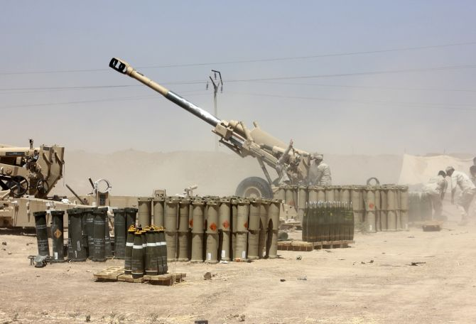 Iraqi security forces fire artillery during clashes with Sunni militant group Islamic State of Iraq and the Levant on the outskirts of the town of Udaim in Diyala province.