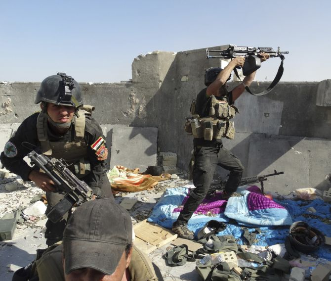 Members of the Iraqi Special Operations Forces take their positions during clashes with the Islamic State of Iraq and the Levant