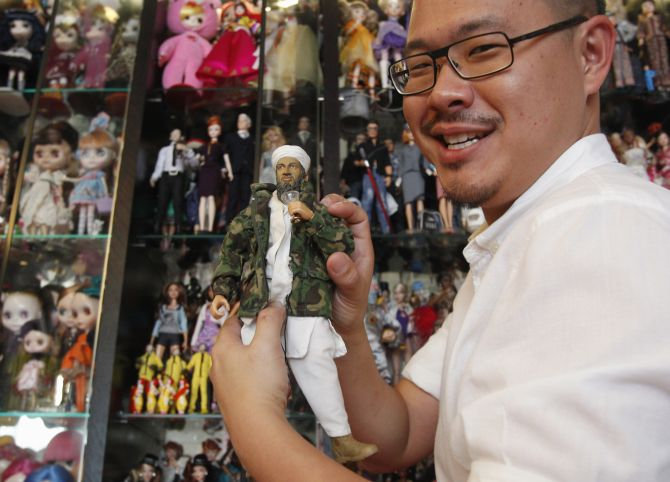 A vendor holds up an Osama bin Laden doll, which became very popular after his death.