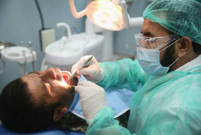 A dentist conducts an oral examination of one his patients.