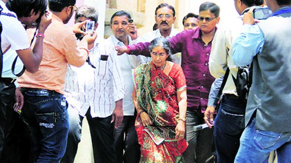 Photographers collect around Jashodaben, Modi's wife, as she goes to cast her vote