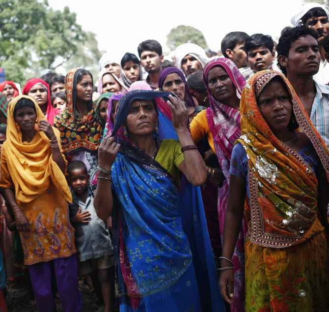 Onlookers stand at the site where two teenage girls were raped and hanged from a tree at Budaun district in UP