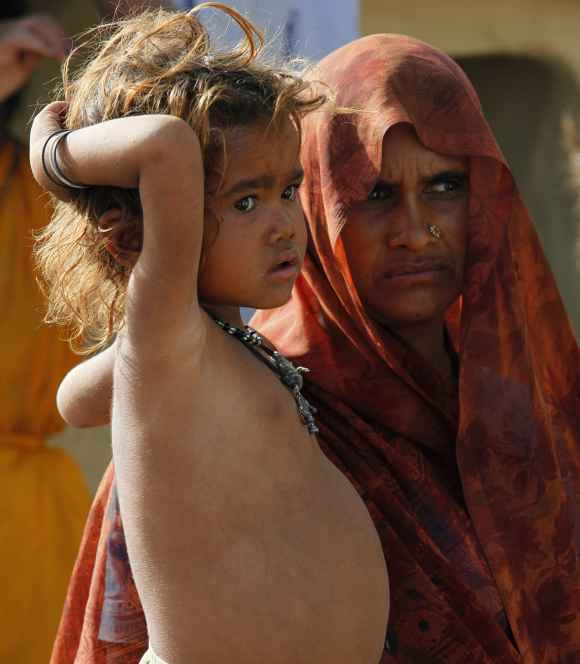 A malnourished child stands next to her mother in UP's Lalitpur district