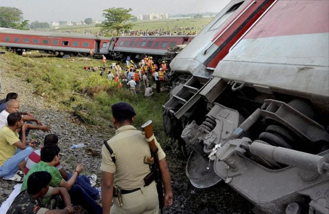 Police stand guard at the derailment spot as NDRF officials tried to look for other passengers