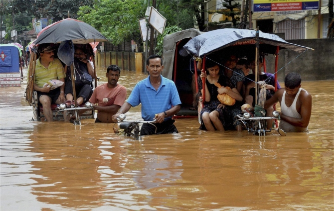 Rickshaw pullers wade through a waterlogged street after heavy rains in Guwahati on Friday.