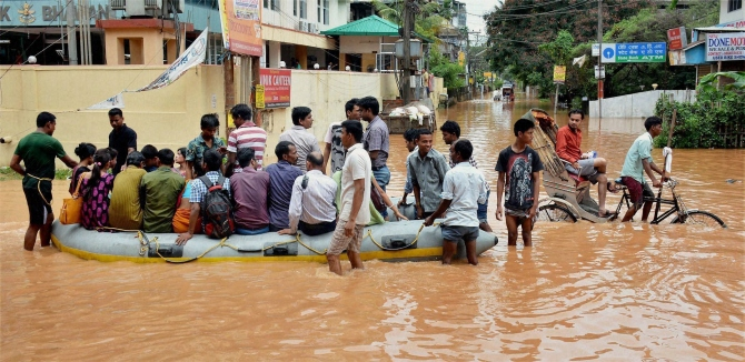 People use rubber boats provided by the district administration to commute in the waterlogged Rajgarh area after heavy rains in Guwahati.