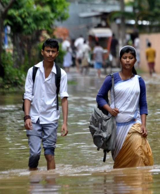 School children wade through water-logged streets in Guwahati