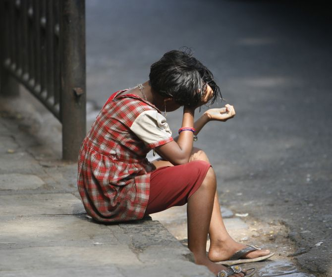 A small girl sits on a Mumbai road with her hand out begging for alms
