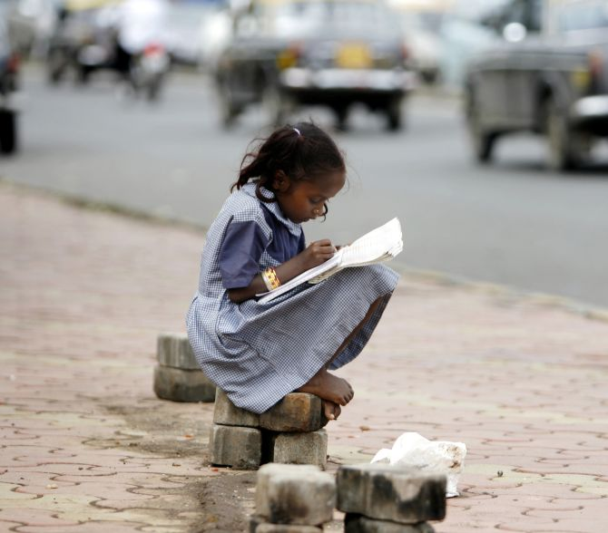 A girl belonging to a homeless family, studies school books at a pavement in Mumbai